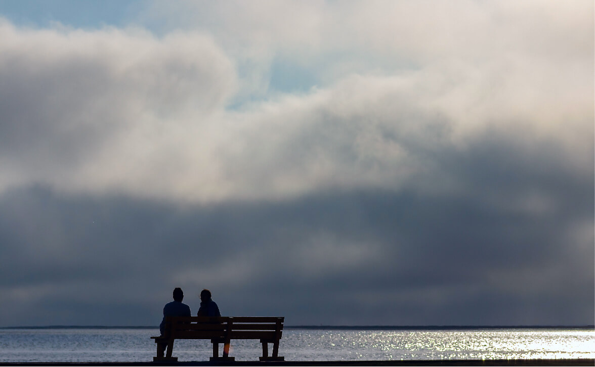 Women sit on bench overlooking ocean